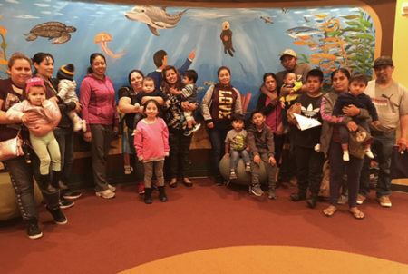 parents and students pose with mural of sea life